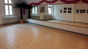 Tanzstudio mit Laminatboden, großem Spiegel und Palmendekoration
