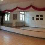 Tanzstudio mit Laminatboden, Spiegelwand, großen Fenstern und Palme.