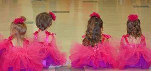 Stundenplan: Kleine Tänzerinnen von hinten, die im Tutu auf dem Boden sitzen.